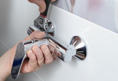 男の手をモンキー レンチと蛇口、シャワーを修正します。