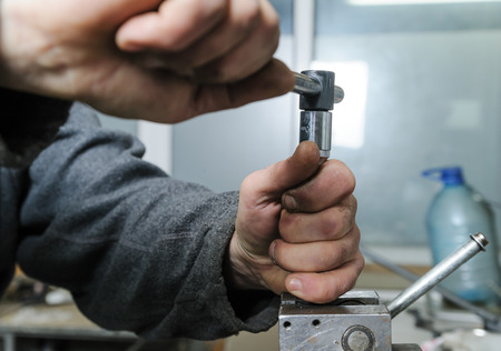 pinched: Mechanics repairing a diesel injector. Mans hand holding a wrench and untwists detail pinched in a vise.