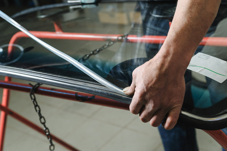 Car mechanics hands are instilling decorative molding to seal of a windshield.