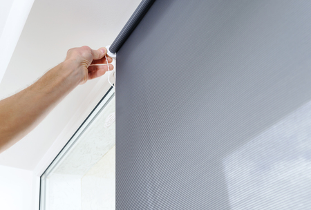 Mans hand is puting a roller blind to a window.