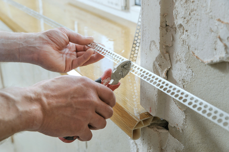 aluminium: Workers hands are cutting a perforated aluminum corner for installation on an external the angle.