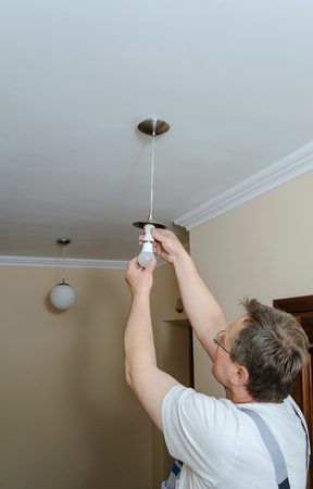 Electrician is installing a LED light bulb in a lamp.