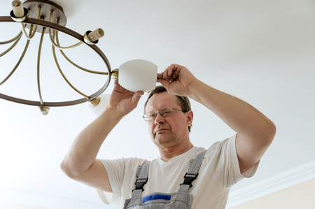 plafond: Electrician is attaching a plafond to a seiling lamp.