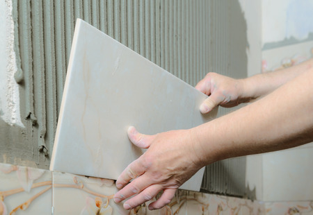 Tilers hands are  installing a ceramic tile on a wall in a bathroom. Stock Photo