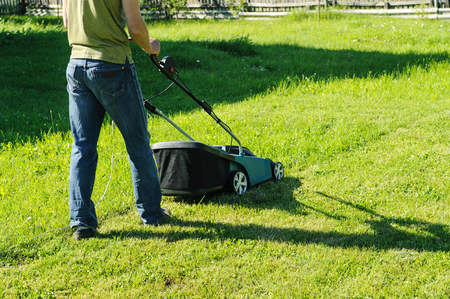 A man is mowing grass with an electric lawn mower. Stock Photo