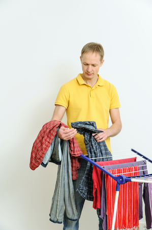 collapsible: The man takes off things from drying rack clothes. Stock Photo