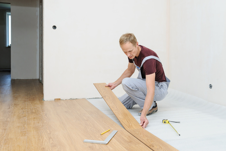 Installation of a laminate floorboard. The worker is attaching one bar after another.