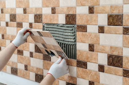 The tiler's hands are installing a tile with holes for electric boxes. Archivio Fotografico