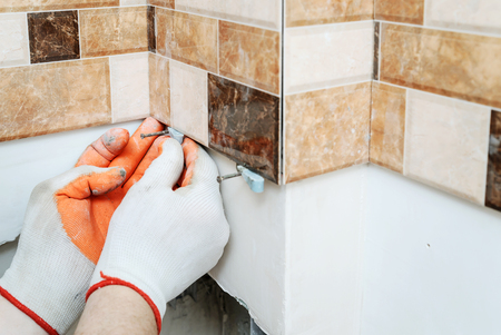 The tilers hands are using plastic wedges to align tiles on the wall.