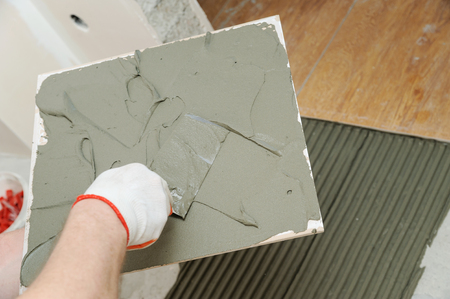 The tilers hand is holding the trowel and putting the adhesive to the tile. Stock Photo