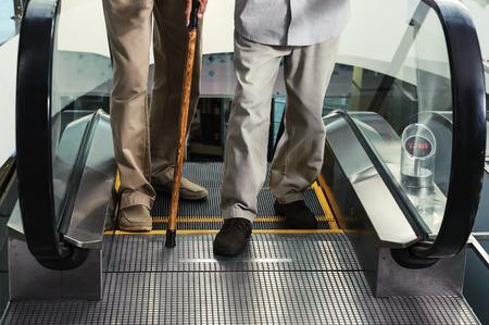 에스컬레이터에서 출구에있는 두 남자 다리. 노인은 막대기에 기대어 있습니다.