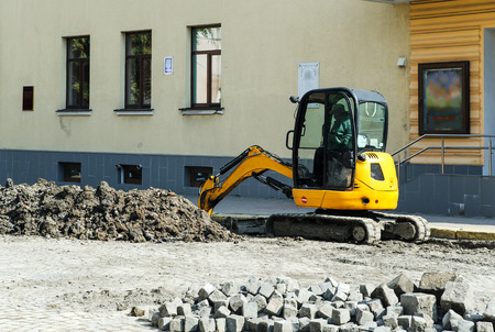 Tractor digger is digging a trench for the installation of water pipes.