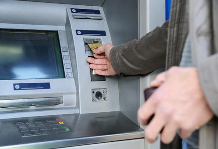 Mężczyzna wkłada kartę bankową do bankomatu.