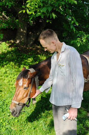 Man is standing next to a horse and stroking his head. Stock Photo