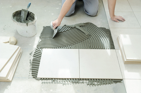 A tiler is putting tiles adhesive to the wall with the notched trowel.