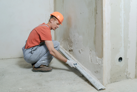 Worker is putting a gypsum plaster on a wall. He is using a long rulerl. Stock Photo