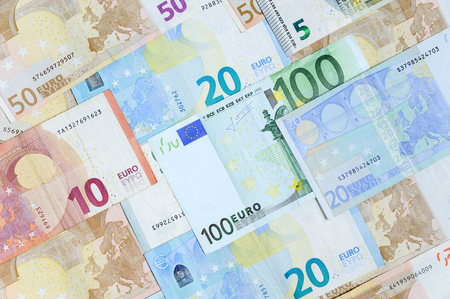 Different euro banknotes are randomly arranged.