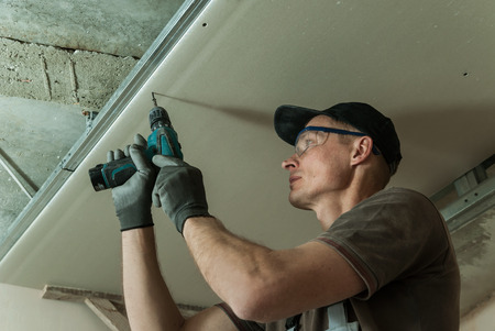Worker fixes the drywall to metal frame using screws Stock Photo