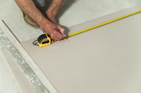 Man measures the drywall to cut a piece required