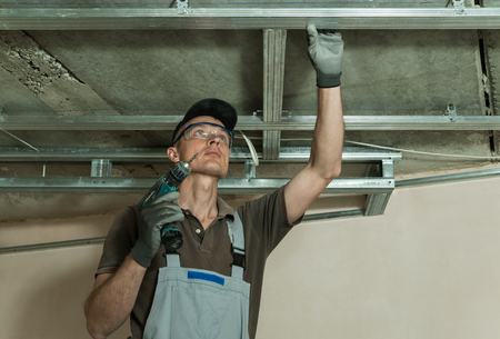 Worker assembles metal frame for plasterboard ceilings