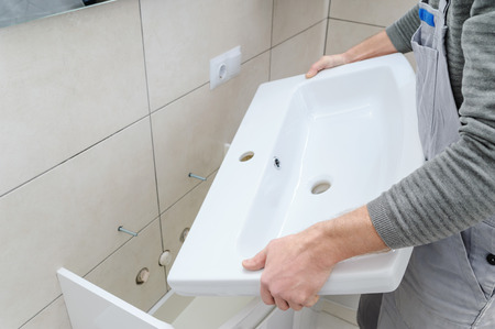 A man is setting the washbasin over the cabinet in the bathroom.