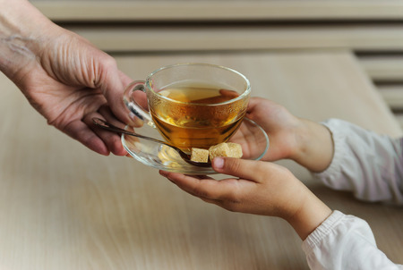 Cup of tea in the childrens hands. The child takes the cup from the hands of an adult
