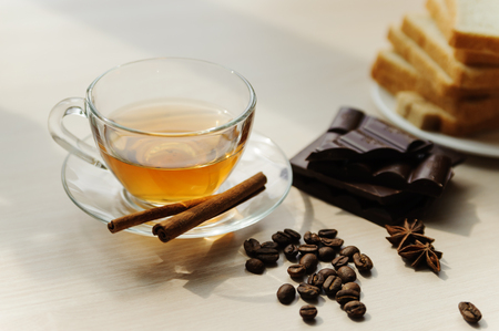 Cup of tea, coffee beans, cinnamon sticks, star anise and chocolate