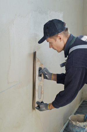 Man gets manually gypsum plaster on the wall Фото со стока - 92905664