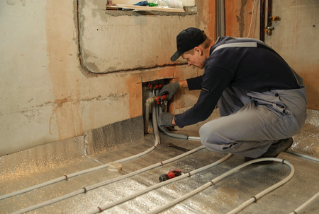 Man working installer connects the underfloor heating pipes