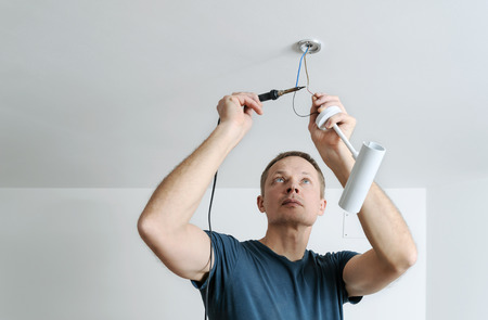 Installing a spotlight in the room. The man is a soldering wire.