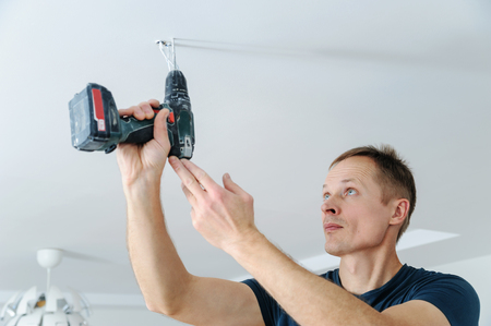 Installing a spotlight in the room. The man is drilling the ceiling to fix the lamp.