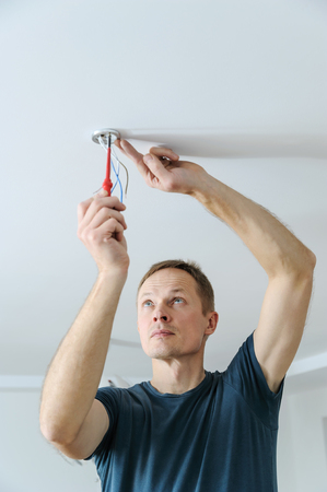 Installing a spotlight in the room. The man is fixing the bracket for the ceiling lamp.