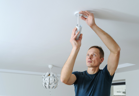 Installing a lamp at home. The man is fixing the spotlight to the ceiling. Фото со стока