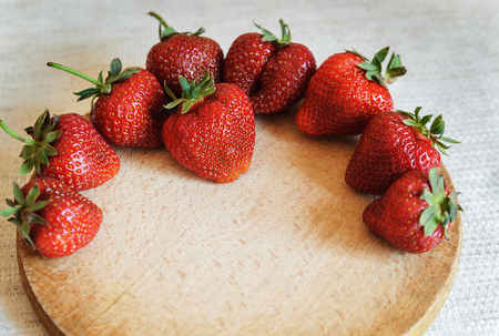 Big ripe strawberries placed on the wooden board