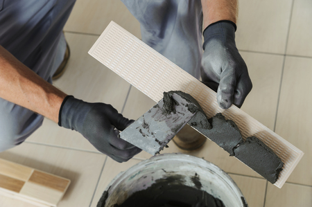 Laying the tiles. Tiler to apply the adhesive on the tile Фото со стока