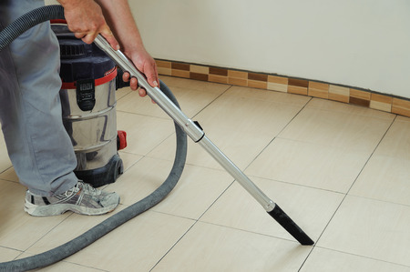 Worker cleans seams between tiles using a vacuum cleaner Фото со стока