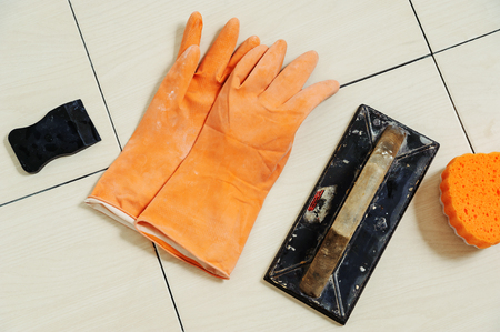 Tools for grouting on tile. Rubber spatula, rubber gloves, rubber float, sponge Фото со стока