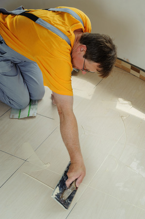 The worker holding a rubber float and filling joints with grout