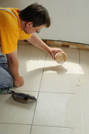 Fill the tile joints. Worker pours grout from the bucket  on the floor