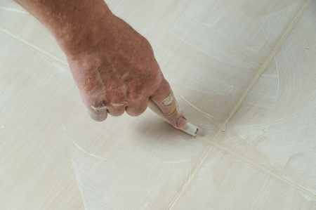 Workers hand smoothing the grout  joints between tiles using a rubber stick Фото со стока