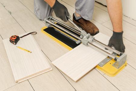 Laying Ceramic Tiles. Tiler cuts tile  manual cutter