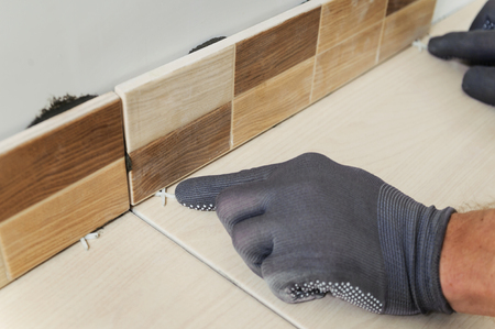 Laying Ceramic Tiles. Tiler aligns the seam between the tiles Фото со стока