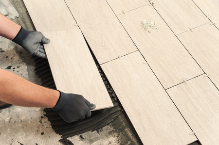 Laying Ceramic Tiles. Man placing ceramic floor tile in position over adhesive Фото со стока