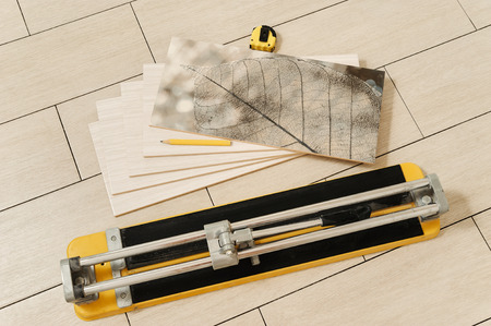 Ceramic tile is composed of a stack. Nearby is the manual cutter, measuring tape and pencil Фото со стока