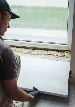Worker installs plastic sill using mounting polyurethane foam