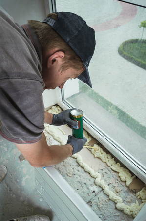 Worker installs plastic sill using polyurethane foam