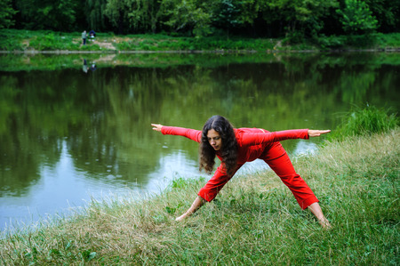 Beautiful young woman performing yogaexercises on the lake. Uttana ashvaroha