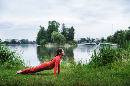 Beautiful young woman performing yoga exercises on the lake. Urdhva mukha svanasana