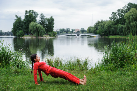Beautiful young woman performing yoga exercises on the lake. Purvottanasana