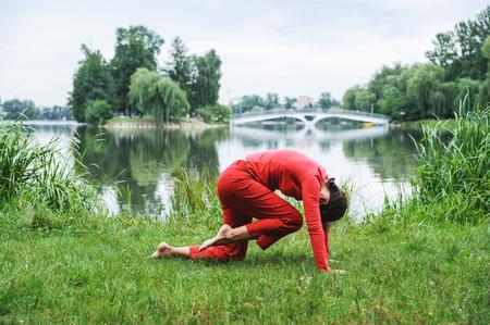 Beautiful young woman performing yoga exercises on the lake. Marjariasana Фото со стока